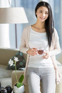 Happy young woman drinking black teaの写真素材 [FYI02857042]