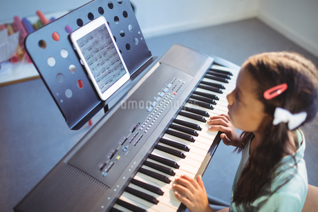 Elementary girl looking at digital tablet on stand while practicing pianoの写真素材 [FYI02857046]