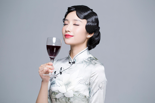 Young beautiful woman in traditional cheongsam with red wineの写真素材 [FYI02857062]