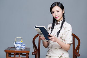 Young beautiful woman in traditional cheongsam reading bookの写真素材 [FYI02857063]