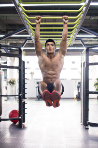 Young man exercising at gymの写真素材 [FYI02857069]
