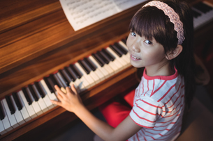 High angle portrait of girl practicing piano in classroomの写真素材 [FYI02857078]