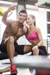 Young couple taking self portrait in the gymの写真素材 [FYI02857085]