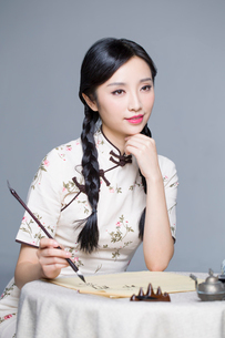Young beautiful woman in traditional cheongsam practicing calligraphyの写真素材 [FYI02857116]