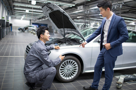 Auto mechanic talking with car ownerの写真素材 [FYI02857117]