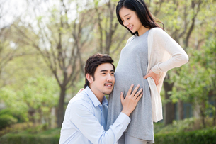 Young father listening to the fetal heartbeatの写真素材 [FYI02857126]