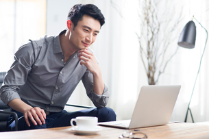 Young man working with laptop in officeの写真素材 [FYI02857127]
