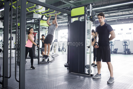 Young adult using exercise machine at gymの写真素材 [FYI02857131]