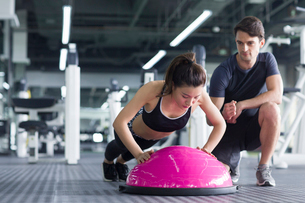 Young woman working with trainer at gymの写真素材 [FYI02857132]