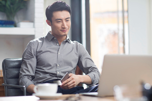 Young man working with laptop in officeの写真素材 [FYI02857134]