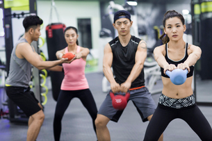 Young adult working with trainer at gymの写真素材 [FYI02857136]