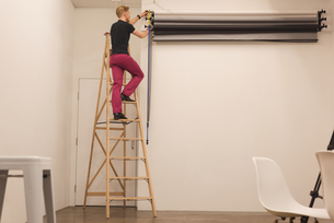 Full length of man on ladder adjusting backdropの写真素材 [FYI02857138]