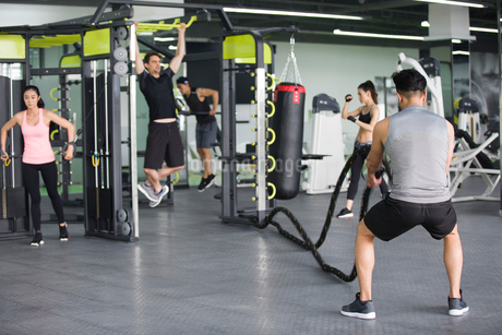 Young adult using exercise machine at gymの写真素材 [FYI02857145]