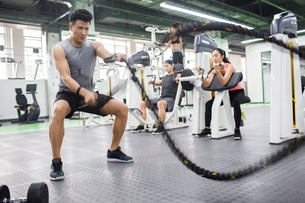 Young man exercising with battling rope at gymの写真素材 [FYI02857148]