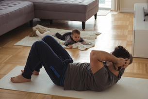 Father doing exercise while baby playing in backgroundの写真素材 [FYI02857162]