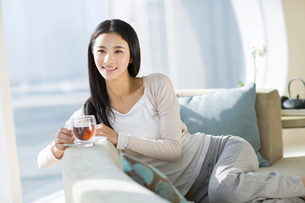 Happy young woman drinking black teaの写真素材 [FYI02857184]