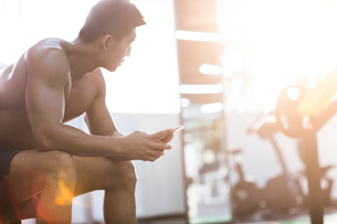 Young man using smart phone in gymの写真素材 [FYI02857193]
