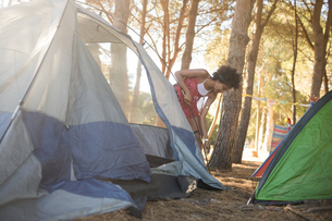 Young woman setting up tent on fieldの写真素材 [FYI02857208]