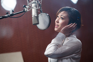 Young woman singing in recording studioの写真素材 [FYI02857215]