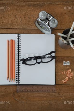 Alarm clock, book, pencil, scale, spectacles and sharpener on wooden tableの写真素材 [FYI02857219]