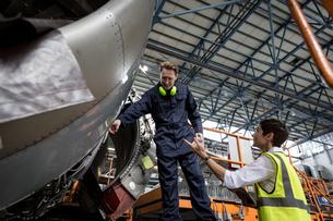 Male aircraft maintenance engineers examining turbine engine of aircraftの写真素材 [FYI02857227]