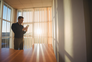 Male executive using digital tablet near window blindsの写真素材 [FYI02857231]