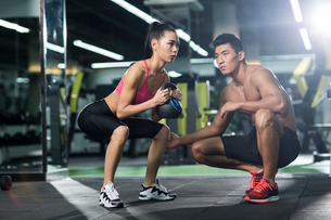 Young woman working with trainer at gymの写真素材 [FYI02857235]