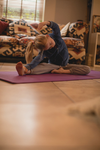 Girl performing yoga in living roomの写真素材 [FYI02857240]