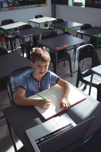 Smiling boy with laptop and book at deskの写真素材 [FYI02857251]