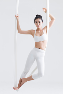 Young Chinese woman practicing aerial yogaの写真素材 [FYI02857259]