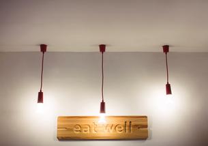 Ceiling lights hanging in front of restaurant boardの写真素材 [FYI02857264]