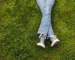 A ten year old girl lying down, legs crossed at the ankles.の写真素材 [FYI02857265]