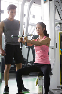 Young woman working with trainer at gymの写真素材 [FYI02857274]
