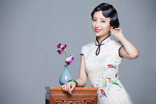 Young beautiful woman in traditional cheongsam with orchidの写真素材 [FYI02857277]