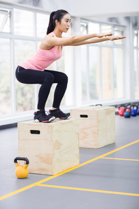 Young woman doing box jump in crossfit gymの写真素材 [FYI02857279]