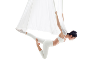 Young Chinese woman practicing aerial yogaの写真素材 [FYI02857299]