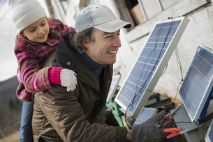 Man giving a child a piggybank while connecting solar powerの写真素材 [FYI02857309]