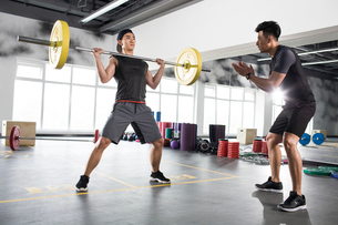 Young man working with trainer at gymの写真素材 [FYI02857321]