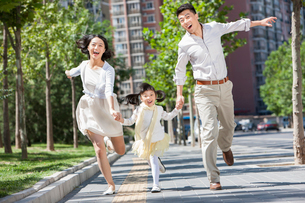 Excited young parents with daughter running on sidewalk hand in handの写真素材 [FYI02857326]