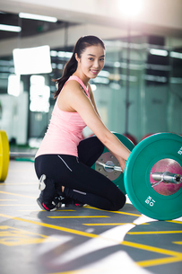 Young woman lifting barbell at gymの写真素材 [FYI02857332]