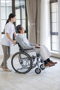 Nursing assistant taking care of senior man in wheel chairの写真素材 [FYI02857342]