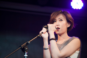 Young woman singing on stageの写真素材 [FYI02857345]