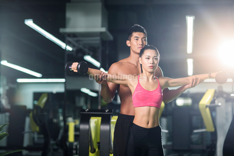Young woman working with trainer at gymの写真素材 [FYI02857349]