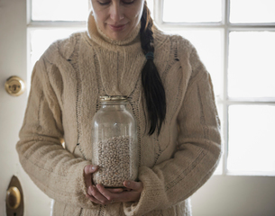 A woman in a jumper holding a glass jar of white beans.の写真素材 [FYI02857357]
