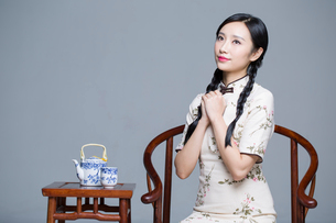 Young beautiful woman in traditional cheongsam with tea setの写真素材 [FYI02857366]
