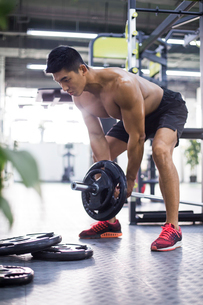 Young man lifting barbell at gymの写真素材 [FYI02857371]