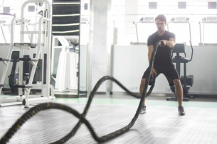 Young man exercising with battling rope at gymの写真素材 [FYI02857379]