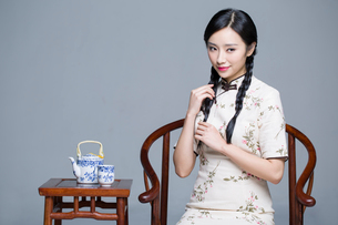 Young beautiful woman in traditional cheongsam with tea setの写真素材 [FYI02857384]