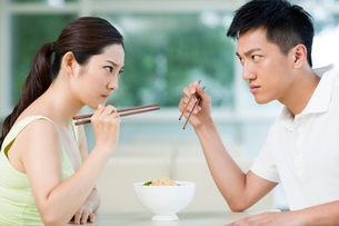 Young couple having noodles in restaurantの写真素材 [FYI02857391]