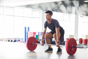 Young man lifting barbell at gymの写真素材 [FYI02857392]